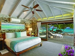 A villa leads directly to the white sand beach at Petit St. Vincent luxury hotel